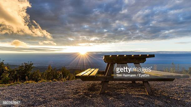 Picnic Table And Bench Against Sunset Sky