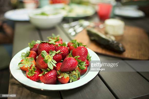 Picnic table with a meal laid out. A place of fresh strawberries.