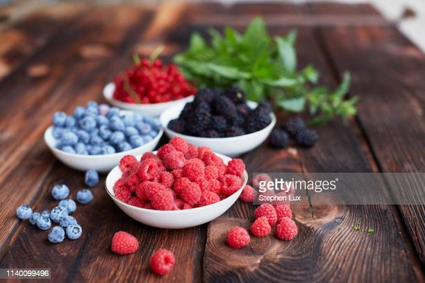 picnic table with four bowls of fresh berries - berry fruit stock pictures, royalty-free photos & images
