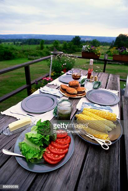 Picnic table with hamburgers and corn
