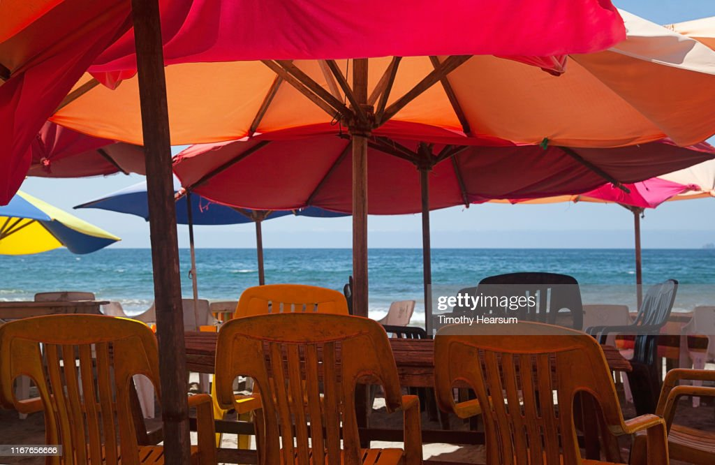Picnic tables and outdoor chairs under bright red umbrellas with ocean beyond; Tenacatita Bay, Costalegre, Jalisco, Mexico : Stock Photo