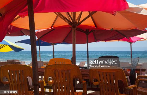 picnic tables and outdoor chairs under bright red umbrellas with ocean beyond; tenacatita bay, costalegre, jalisco, mexico - timothy hearsum stock pictures, royalty-free photos & images