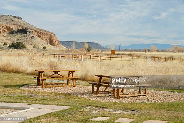 Picnic tables in prairie with mountains in distance