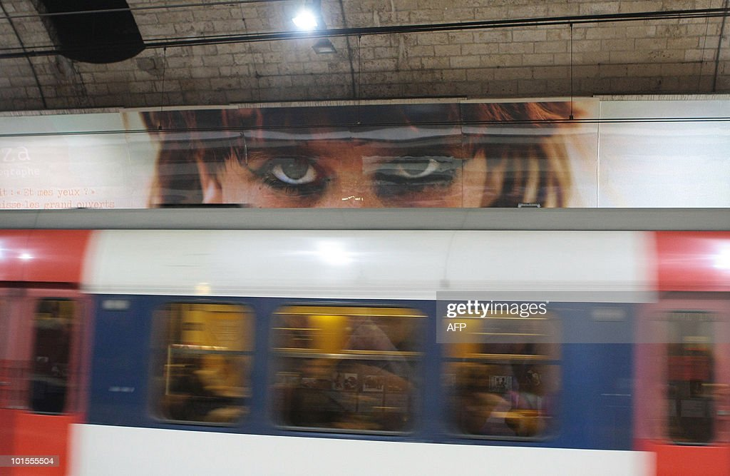 A picture by Iranian photographer Reza Deghati, is seen behind a train, during an exhibition in the Paris's subway at the Luxembourg station on June 2, 2010 in Paris. The exhibition, intitled 'Chemins Paralleles' runs until September 12, 2010.