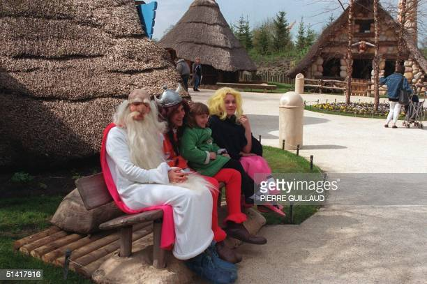 Picture dated 04 April 1990 shows a child posing for a picture with some characters of the Asterix leisure parc in Plailly near Paris