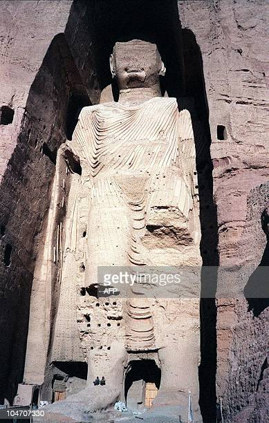 Picture dated 07 December 1997 shows two Afghans sitting under the world's tallest standing statue of Buddha in central Bamiyan province of...