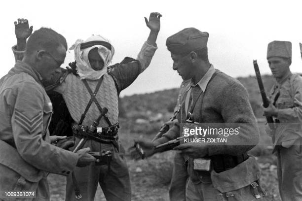 A picture dated 13 December 1938 shows Jewish settlement police members disarming an Arab marauder caught near Kibbutz Ramat David during the Arab...