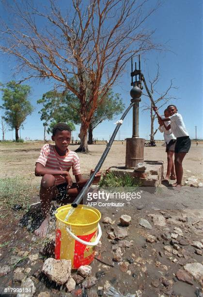 Picture dated 13 February 1992 shows South African children filling a bucket of water the village's well An international conference water management...
