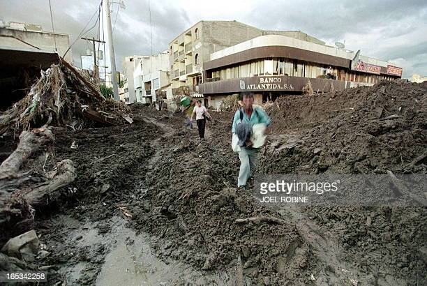 Picture dated 13 November of local residents walking through an area of Tegucilgalpa recovered with mud after the passage of hurricane Mitch Local...