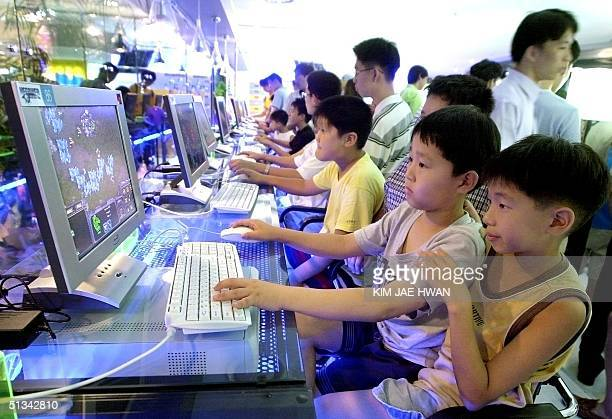 Picture dated 18 August 2001 shows South Korean children enjoying games on the Internet in a highspeed cyber station in the central city of Taejon...