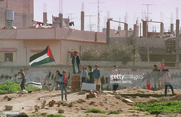 - Picture dated 18 February 1988 showing Palestinian children throwing stones and waving Palestinian flags during the demonstrations in the Nuseirat...