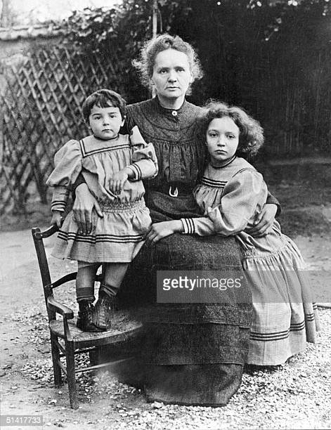 Picture dated 1908 shows Marie Curie posing with her two daughters Eve and IrFne in their home's garden. Marie Curie and her husband, the French...