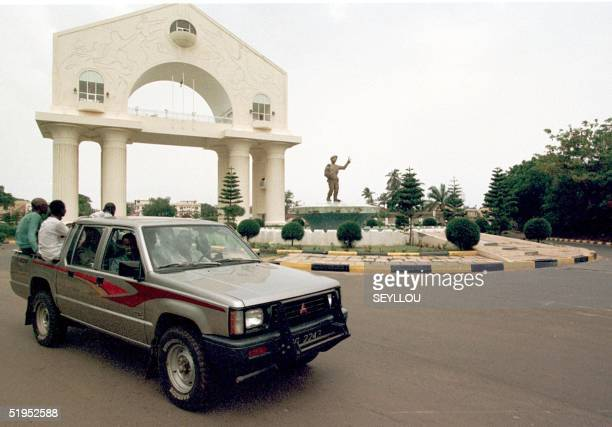 Picture dated 24 June 1999 shows a car passing by the monument ericted in honour of President Yahya Jammeh in Banjul. Gunfire were heard near the...