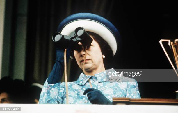 Picture dated May 1972 shows Queen Elizabeth II looking at horse races with binoculars at Longchamp