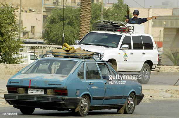 Picture dated November 20 2007 shows private security personnel ordering an Iraqi civilian driver to clear the way for an official convoy in central...