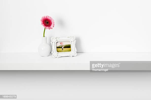 Picture frame and daisy flower on shelf