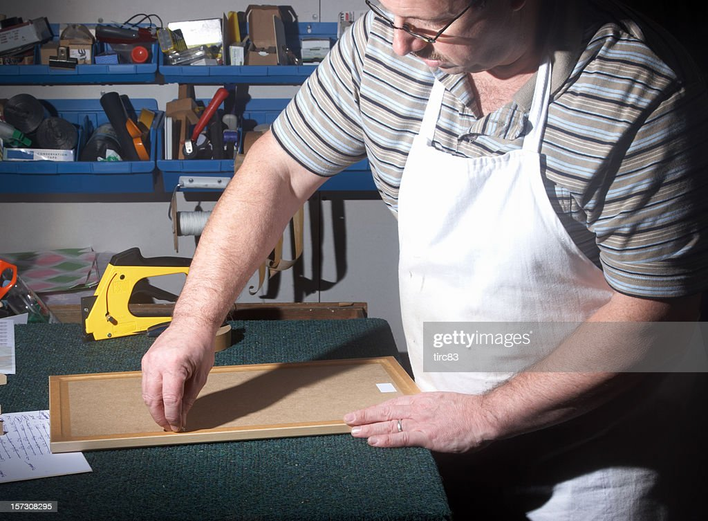 Picture framer at work taping : Stock Photo