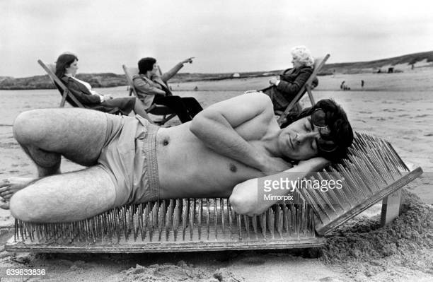 A picture from a series of humurous novelty images taken by Sunday People photographer Dennis Hutchinson A sunbathing man relaxes on a bed of nails...