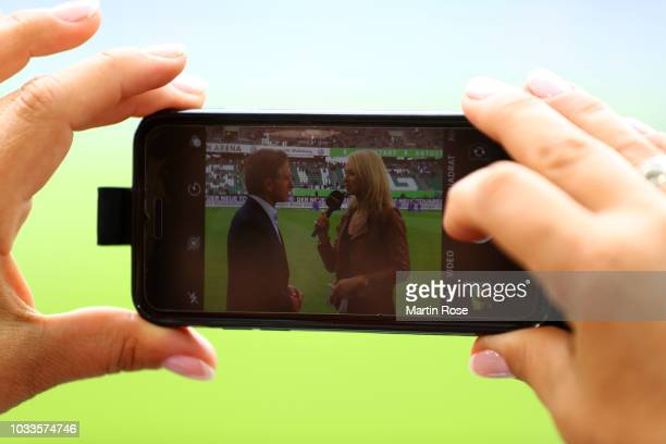 A picture is taken on a phone while Bruno Labbadia Manager of Vfl Wolfsburg is interviewed ahead of the Bundesliga match between VfL Wolfsburg and...