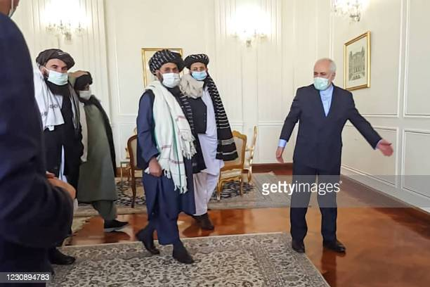 Picture obtained by AFP from the Iranian news agency Tasnim on January 31 shows Iran' Foreign Minister Mohammad Javad Zarif meeting with Mullah Abdul...