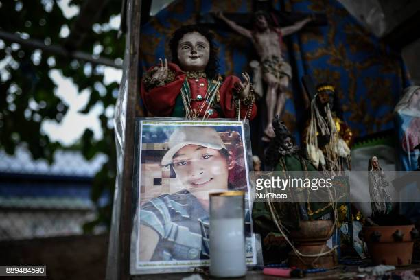 A picture of 16yearold Jerico Garcia who was killed by unidentified assailants is seen next to religious statues at his shanty in Quezon city Metro...
