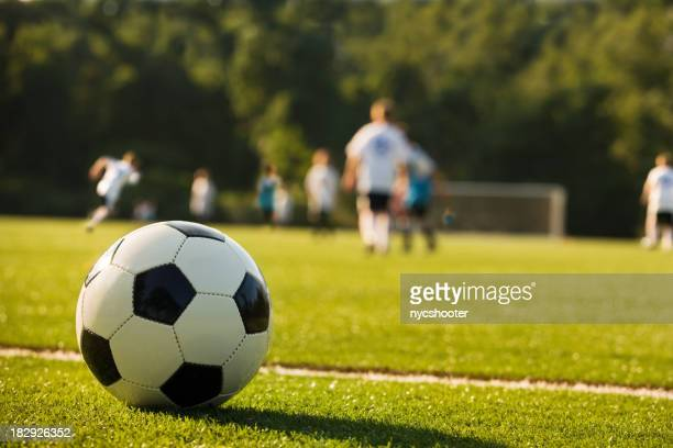 Picture of a football with kids playing in the background