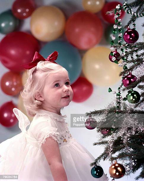1959 A picture of a happy little girl wearing a smart white dress with also a red ribbon in her hair whilst she is looking at a christmas tree...