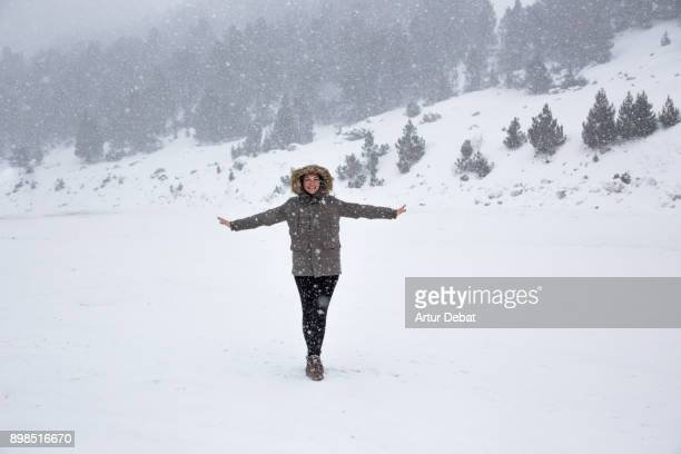 Picture of a happy woman enjoying winter huge snowfall in the Andorra Pyrenees during Christmas travel vacations.