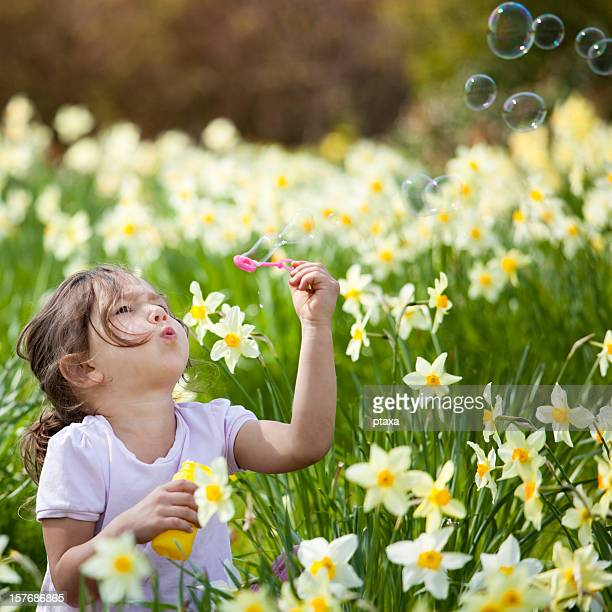 A picture of a little girl blowing bubbles in a flower field