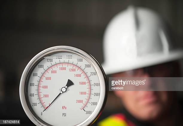 a picture of a man looking at a gauge - pressure gauge stock photos and pictures