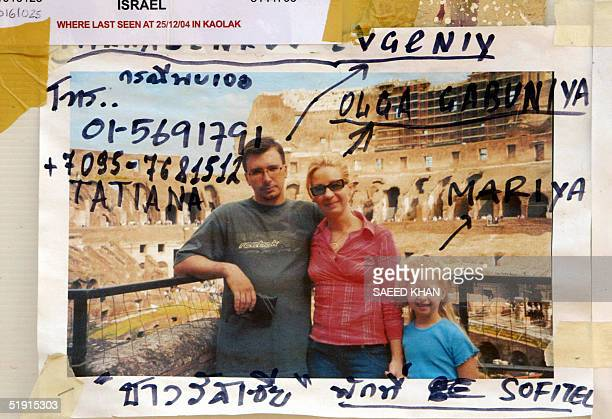 A picture of a missing Russian family from Sofitel resort is displayed on a board at a relief camp in Khao Lak beach 05 January 2005 Ten days after...