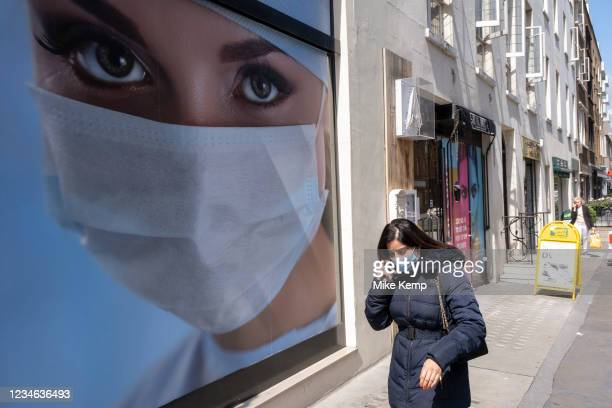 Picture of a model wearing a face mask adorns an advertisement for medical premises in Marylebone on 10th August 2021 in London, United Kingdom....