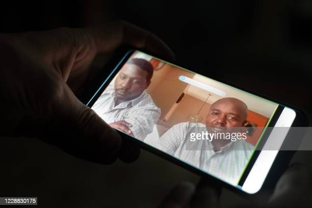 Picture of a monitor of a smartphone taken in Kigali, Rwanda, on October 1, 2020 shows the sons of Paul Rusesabagina, the polarising hero of the...
