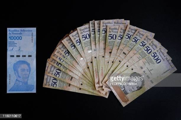 Picture of a new ten thousand Bolivar-note and its equivalent in current five hundred Bolivar-bills in Caracas on June 14, 2018. - Venezuela is again...