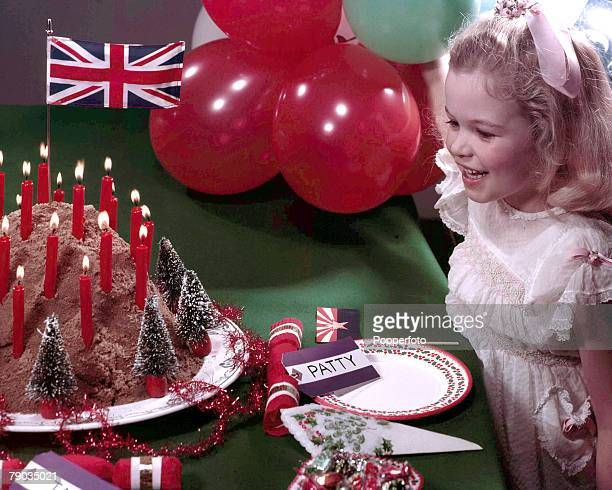 1958 A picture of a small happy young girl wearing a smart white dress standing a table looking at a christmas cake which is decorated with small...