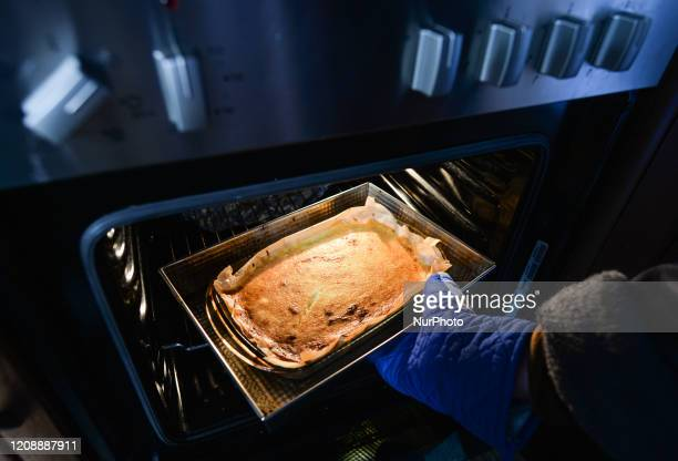A picture of a woman taking a homemade cheesecake out of an oven inside her appartment during the coronavirus lockdown in Krakow On Wednesday April 1...
