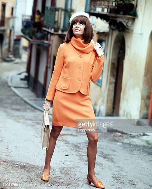 A picture of a young woman wearing a fashionable orange outfit smiling for the camera whilst walking along an old street