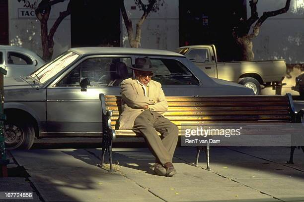 Picture of an elderly man elegantly dressed napping in the shadow on a sunny afternoon in the colonial town of Sucre, Bolivia.