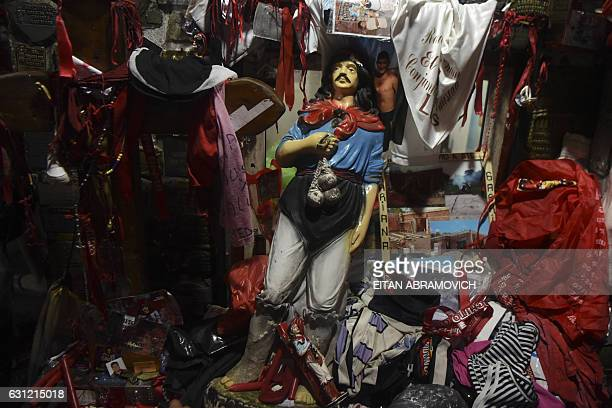 Picture of an image of folk saint Gauchito Gil and different offerings left by pilgrims at his sanctuary near Mercedes in the Argentine province of...