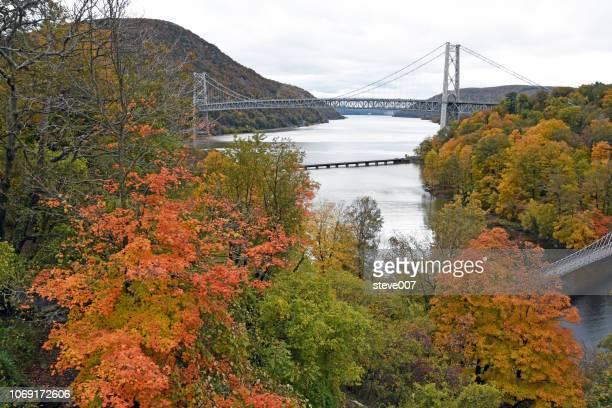 picture of bear mountain bridge taken in highland falls, new york in orange county with the changing color of the tree's. - bear mountain bridge stock pictures, royalty-free photos & images