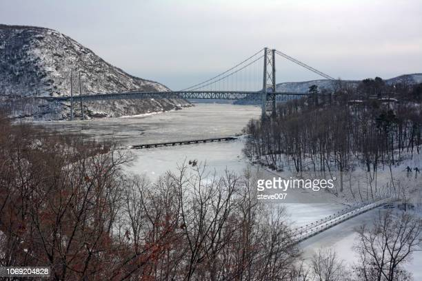 picture of bear mountain bridge taken in highland falls, new york in orange county showing the snow covered mountain on the westchester county side of the bear mountain bridge and ice on popolopen creek and the hudson river. photo taken saturday february - bear mountain bridge stock pictures, royalty-free photos & images