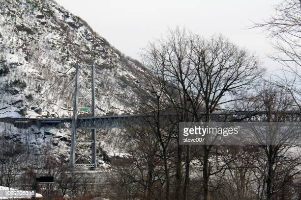 picture of bear mountain bridge taken in highland falls, new york in orange county showing the snow covered mountain on the westchester county side of the bear mountain bridge and the hudson river. photo taken saturday february - bear mountain bridge stock pictures, royalty-free photos & images