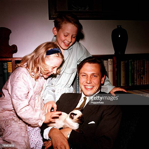 1962 A picture of British naturalist and broadcaster David Attenborough at home with two of his children as they play with their pet cat
