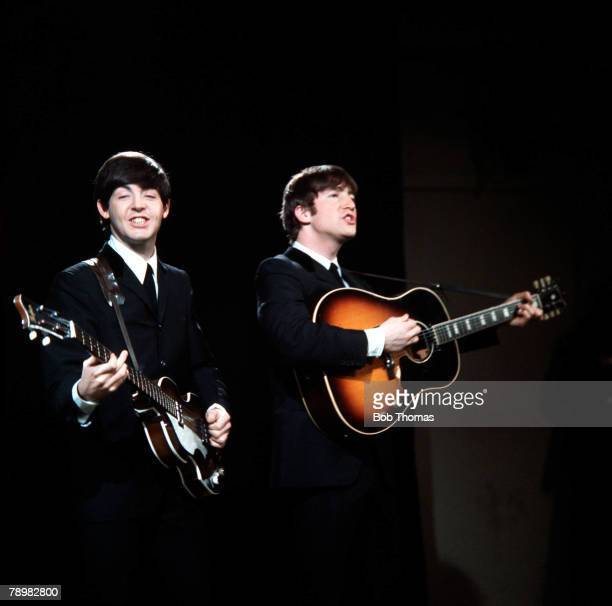 1964 A picture of British pop group The Beatles in action as John Lennon and Paul McCartney play guitar and sing
