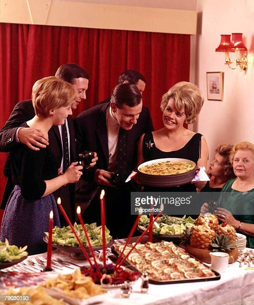 Picture of British television presenter Judith Chalmers hosting a dinner party at her house, as she attends to her guests who include fellow British...