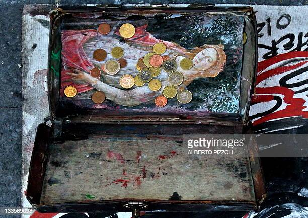 Picture of Euro coins in the box of a street performer taken on November 20, 2011 in central Rome. AFP PHOTO / ALBERTO PIZZOLI