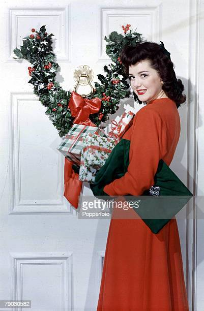 1953 A picture of film actress Ann Rutherford standing with Christmas presents next to a door decorated with a holly wreath