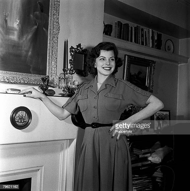 Picture of film actress Joan Rice posing next to her fireplace