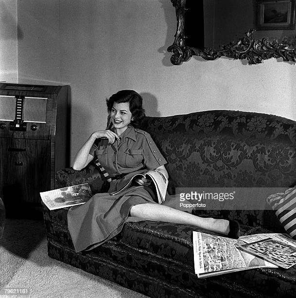 Picture of film actress Joan Rice relaxing on a settee reading a magazinne