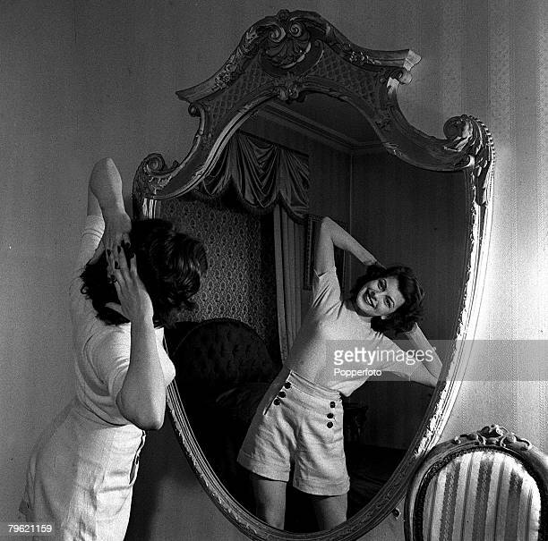 Picture of film actress Joan Rice stretching in front of a mirror